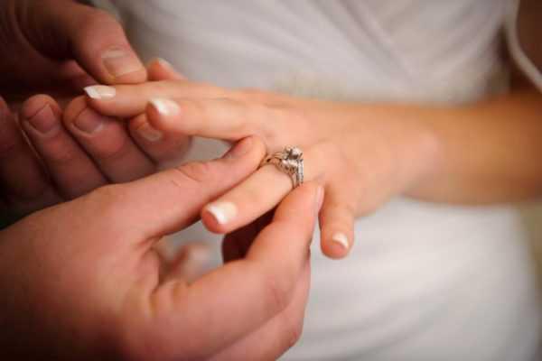 Мужчина одевает женщине кольцо